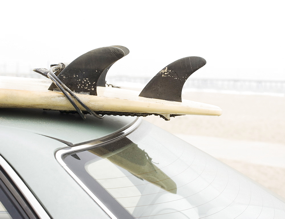 Close up of surfboard on top of car at beach