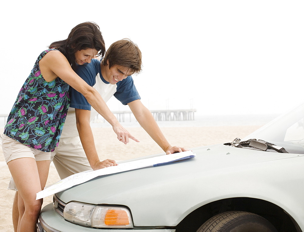 Couple looking at map on car hood at beach