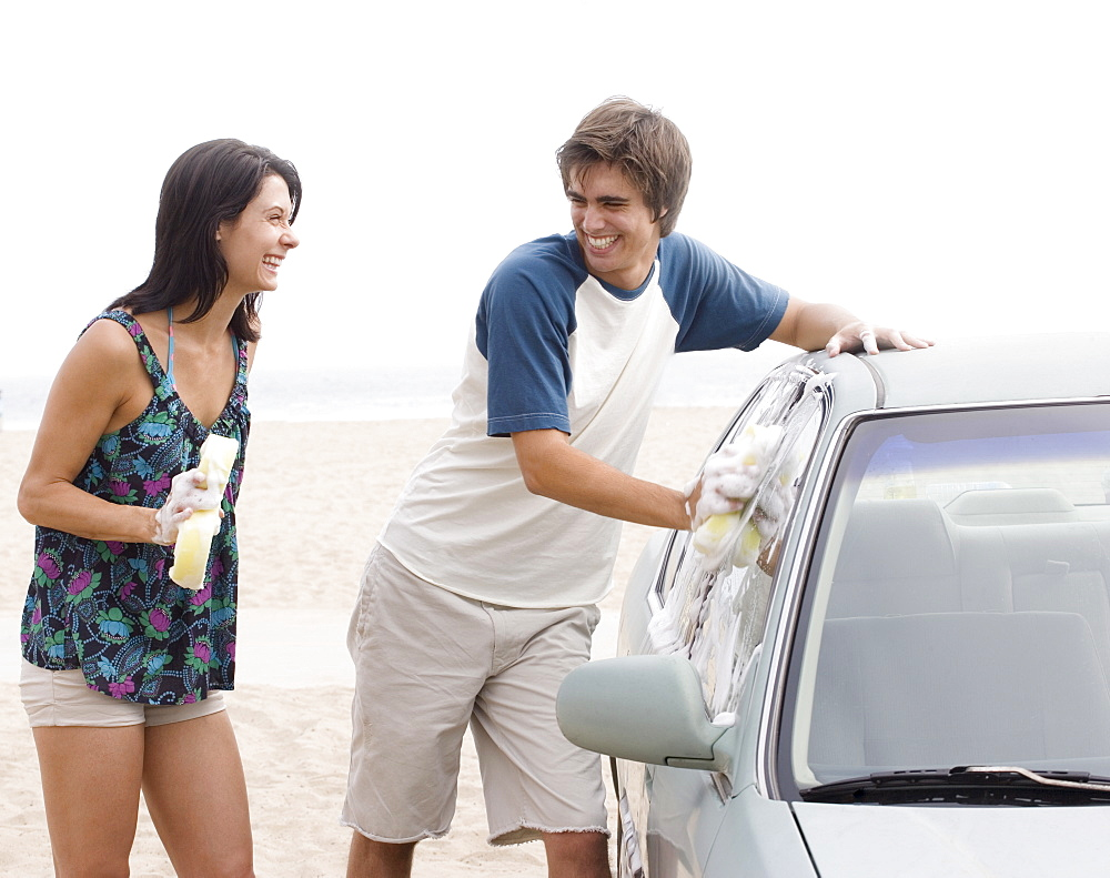 Couple laughing next to car at beach
