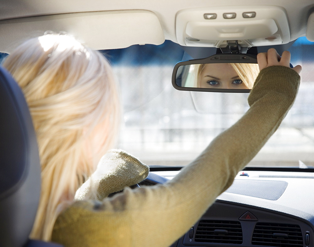 Woman adjusting car rear view mirror