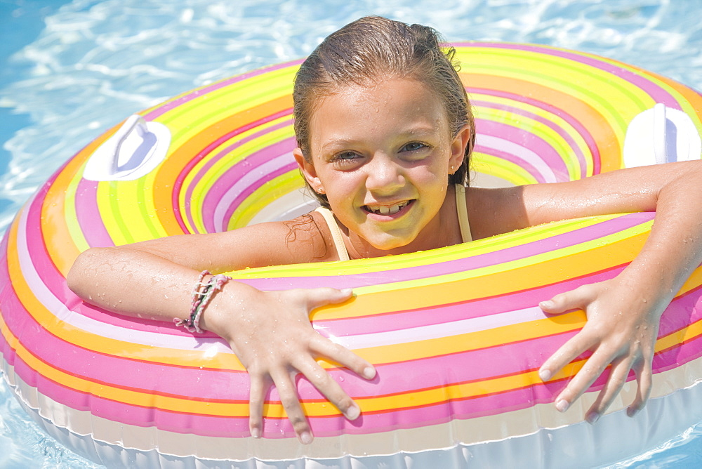 Girl playing in inflatable tube in swimming pool