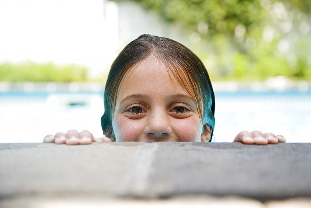 Girl peeking over edge of swimming pool - 1178-16642