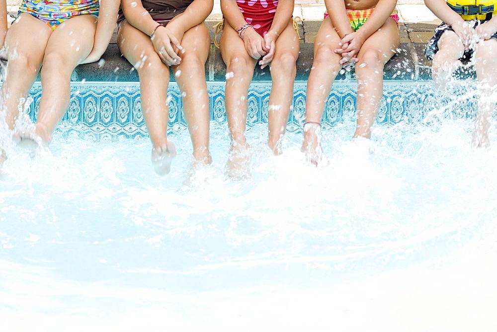 Girls splashing feet in swimming pool