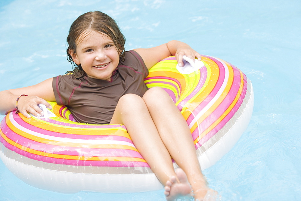 Girl floating in inflatable ring in swimming pool