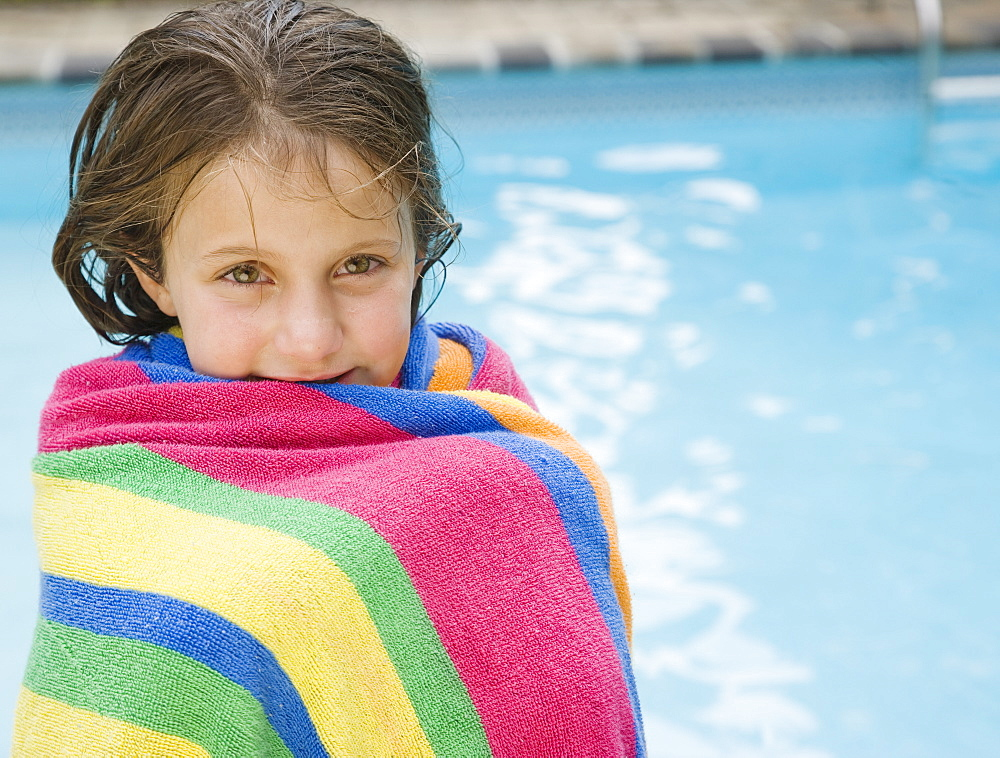 Girl wrapped in a towel at edge of swimming pool
