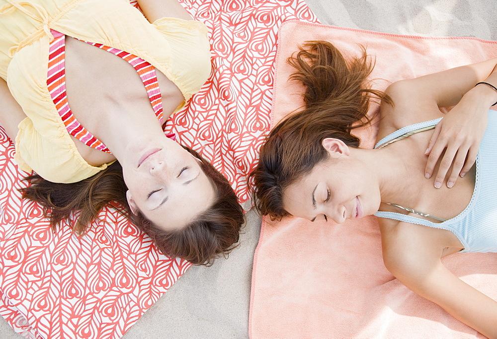 Women laying on beach blankets