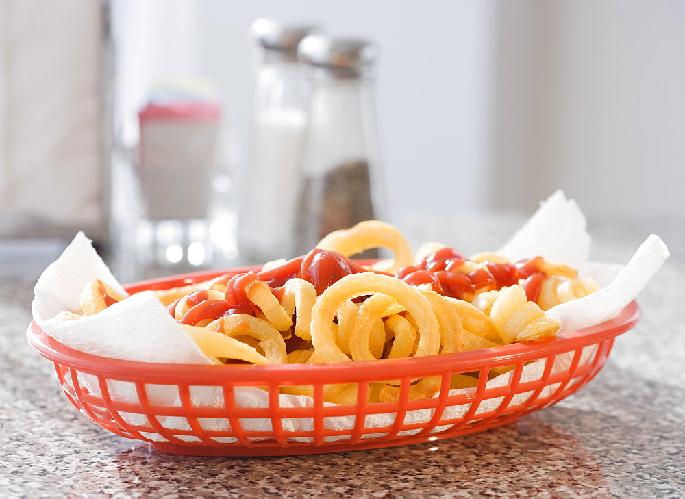 Close up of French fries and ketchup in basket
