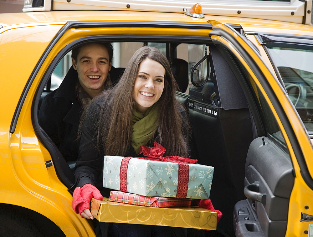 Couple with gifts getting out of taxi cab