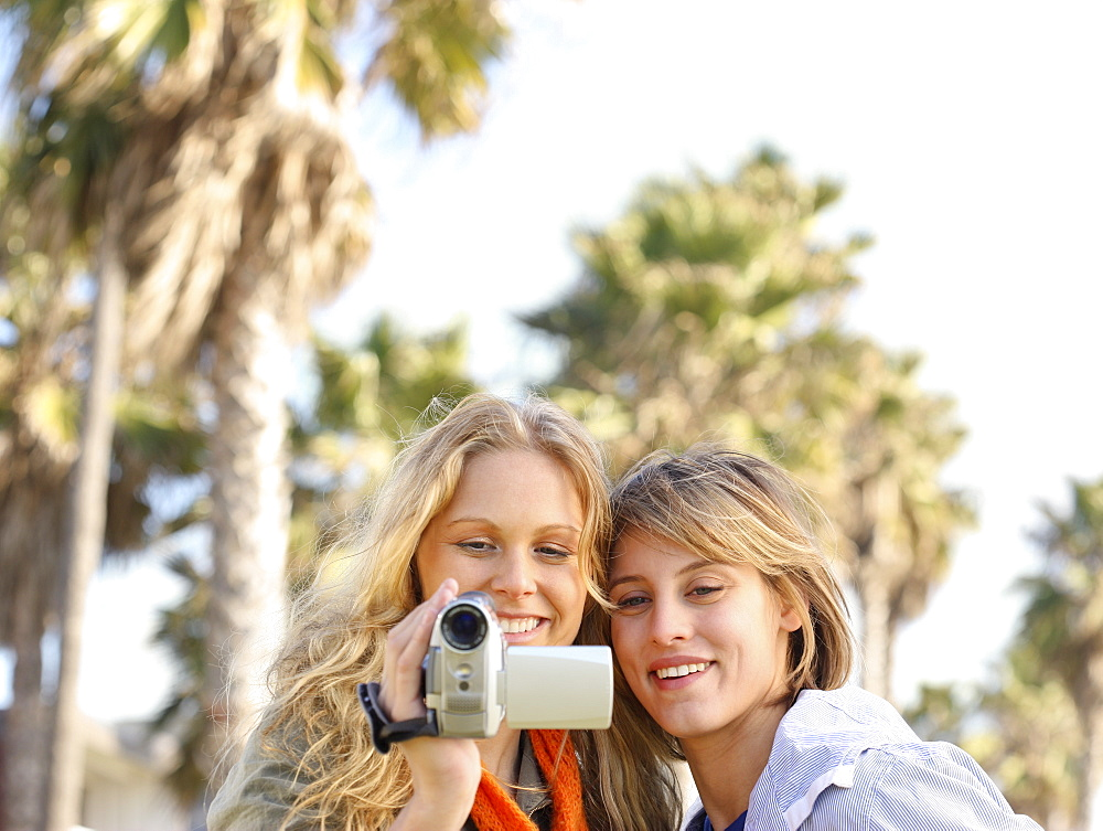 Two women looking at video camera
