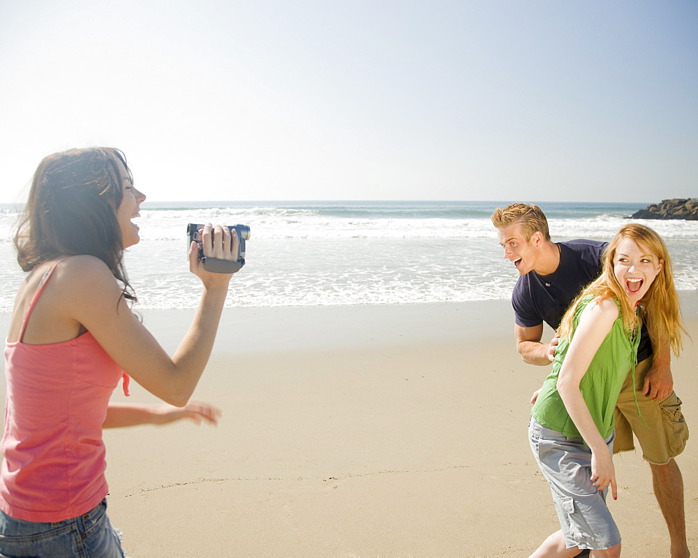 Woman video recording friends at beach