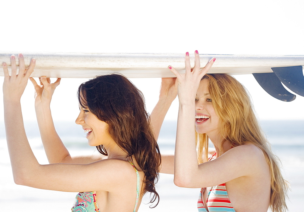 Two women holding surfboard on heads
