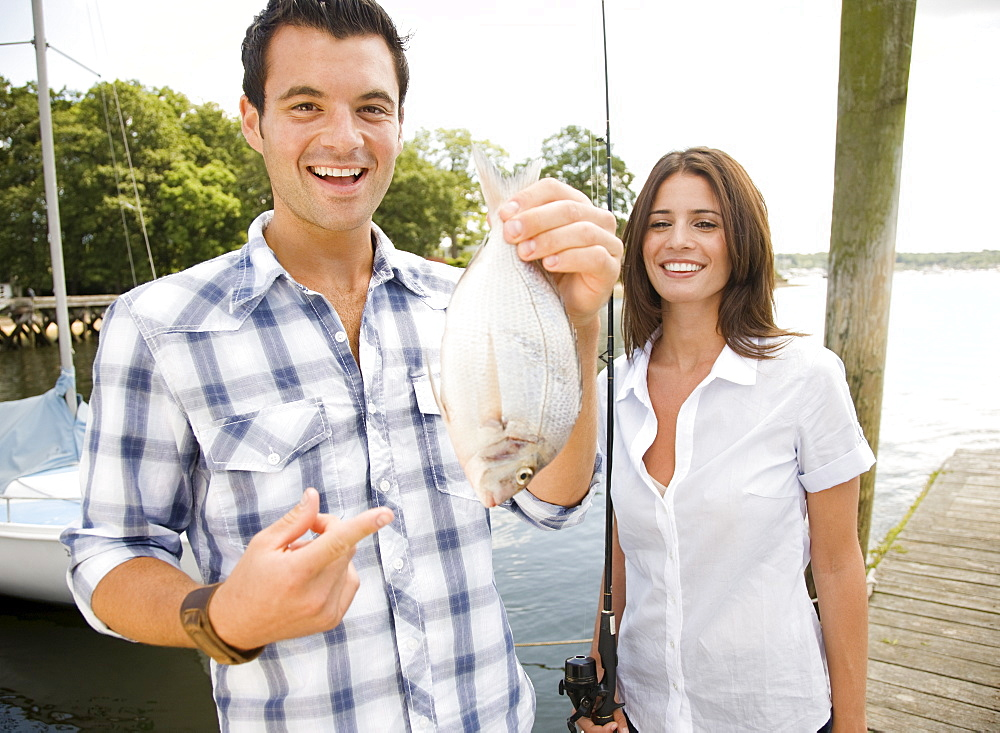 Portrait of couple holding freshly caught fish