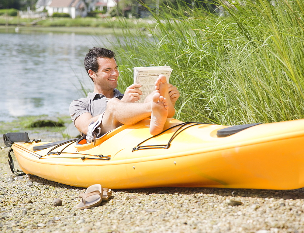 Man reading newspaper in kayak