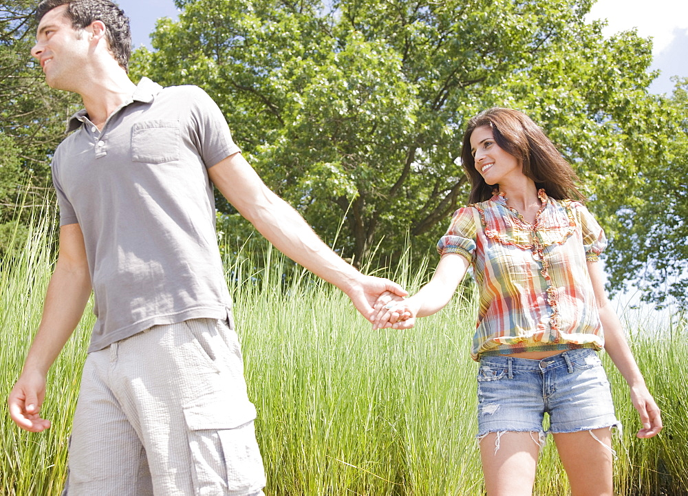 Couple holding hands and walking through reeds