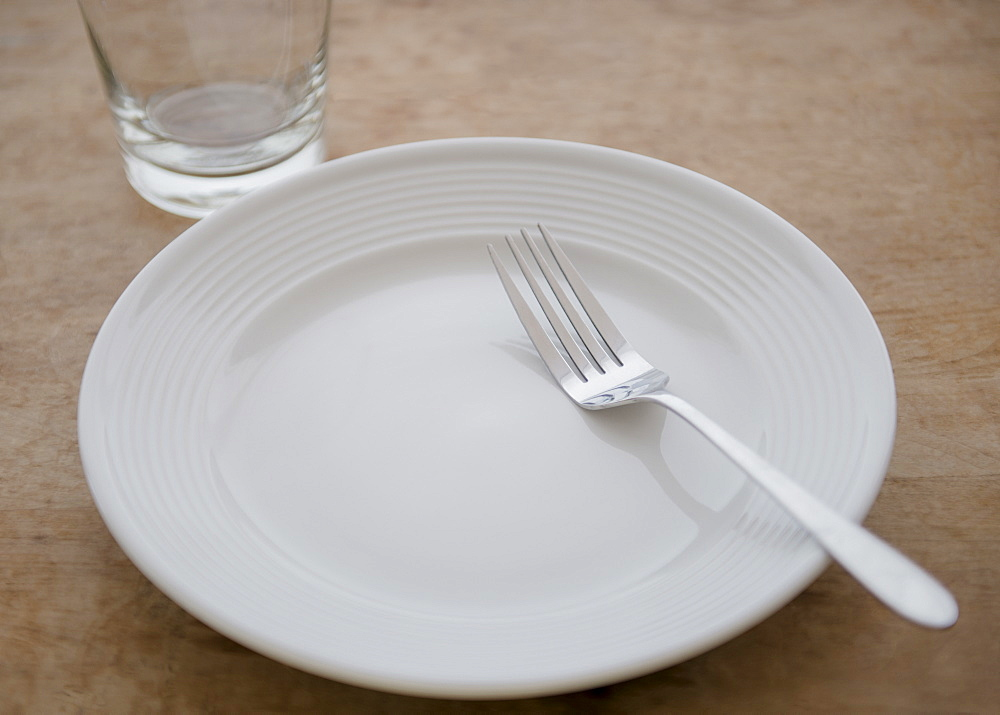 White plate with fork and glass