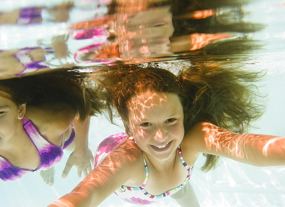 USA, New York, Girls (10-11, 10-11) in swimming pool