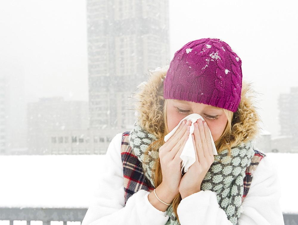USA, New Jersey, Jersey City, woman blowing nose