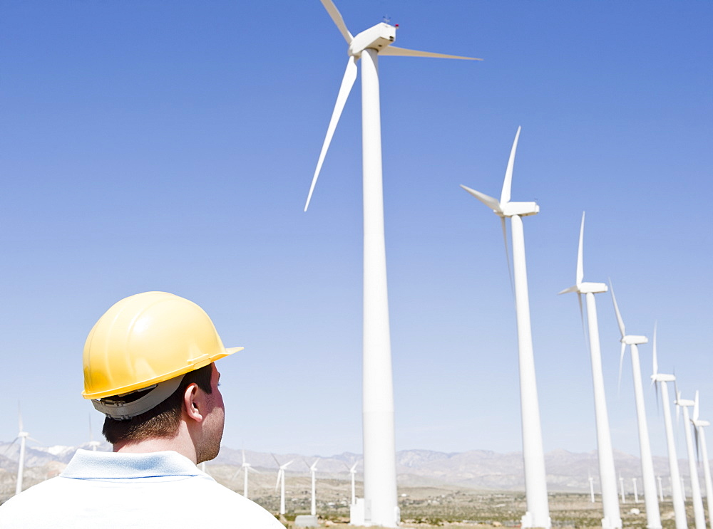 USA, California, Palm Springs, Coachella Valley, San Gorgonio Pass, Man in hard hat looking at wind turbines