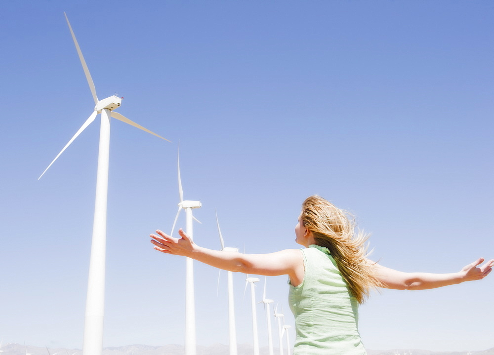 USA, California, Palm Springs, Coachella Valley, San Gorgonio Pass, Rear view of woman stretching arms and looking at wind turbines