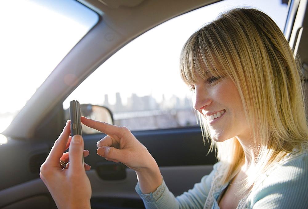 USA, Brooklyn, Williamsburg, Woman using smart phone in car