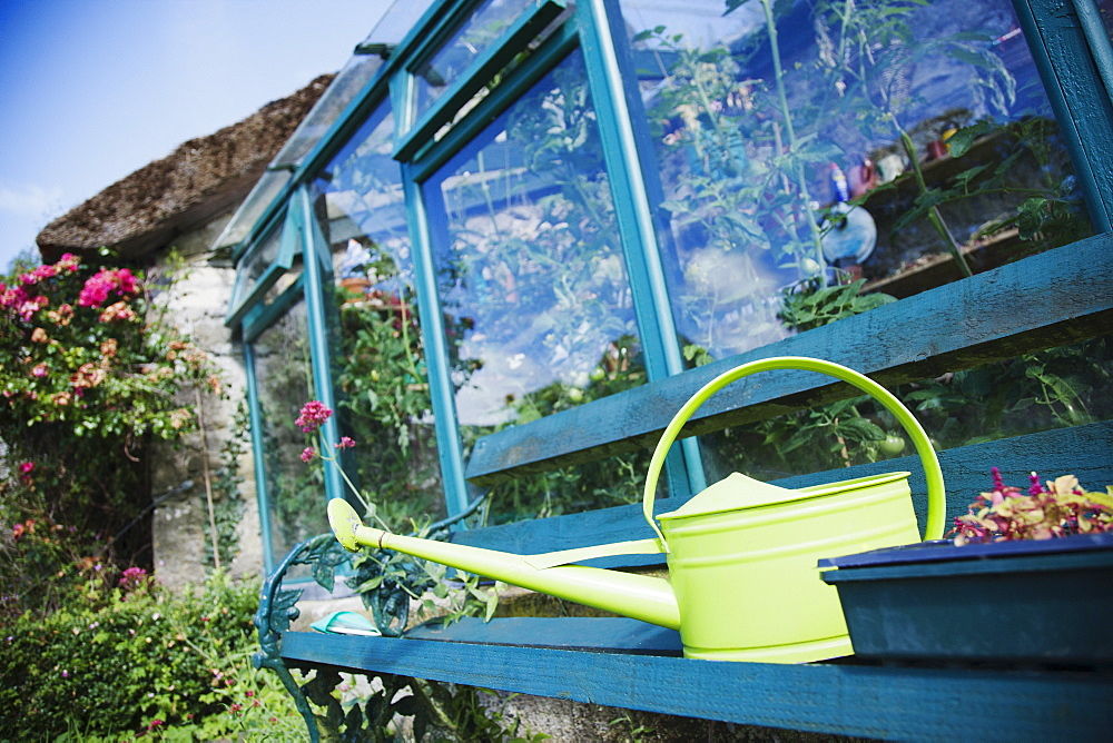 Ireland, County Westmeath, Watering can in front of greenhouse
