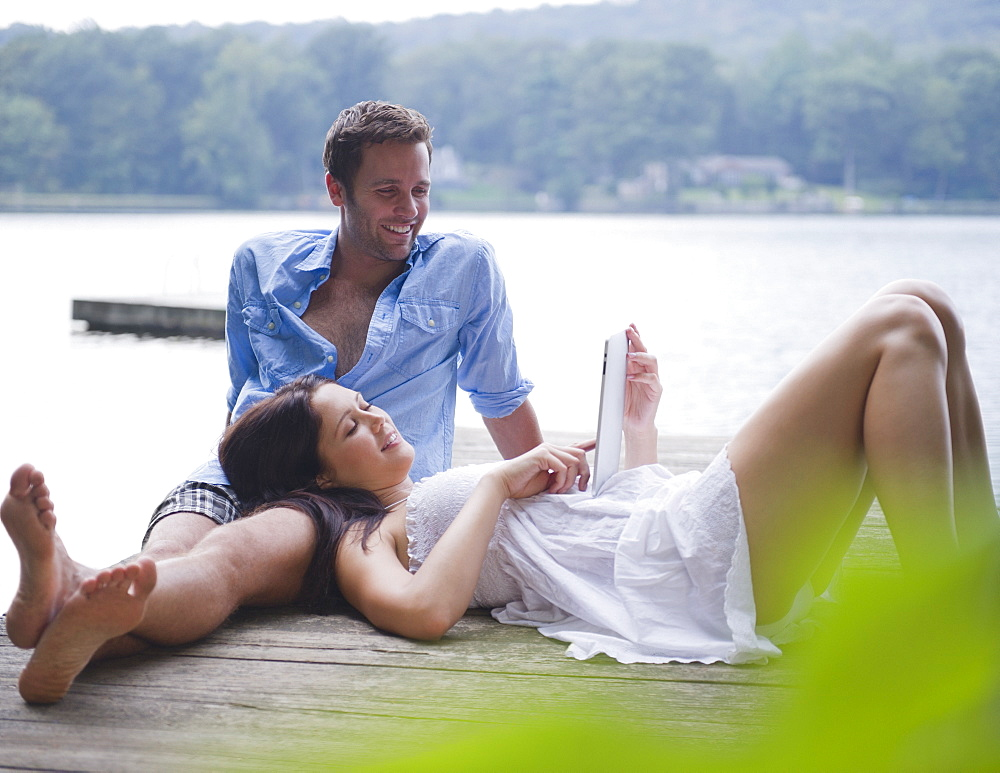 USA, New York, Putnam Valley, Roaring Brook Lake, Couple relaxing on pier by lake
