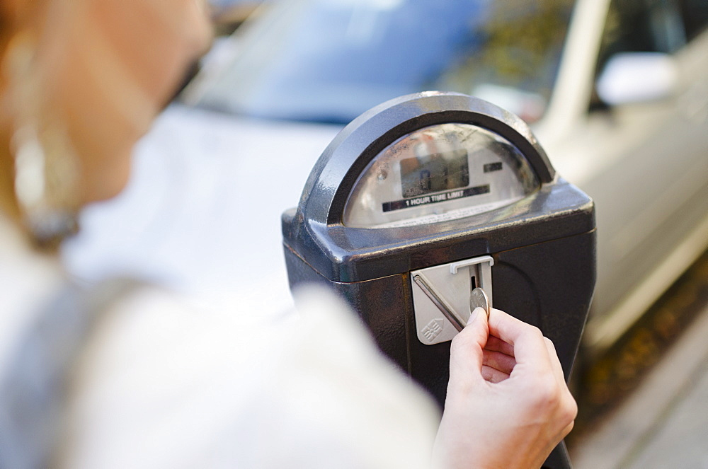 USA, New York State, New York City, Brooklyn, Woman inserting coin into parking meter