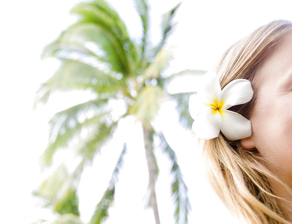 Woman wearing plumeria flower in hair, USA, Hawaii, Kauai, Poipu Beach