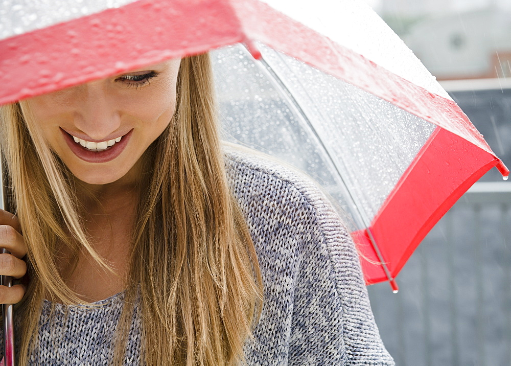 Smiling young woman with umbrella in rain