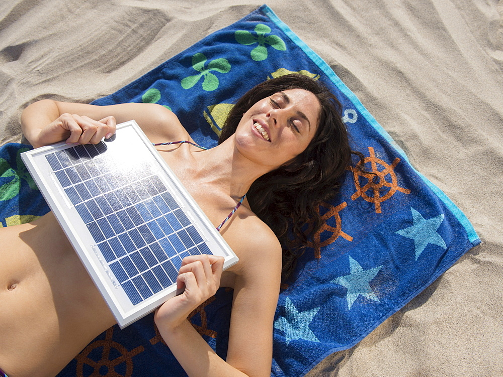Woman sunbathing with solar panel at beach