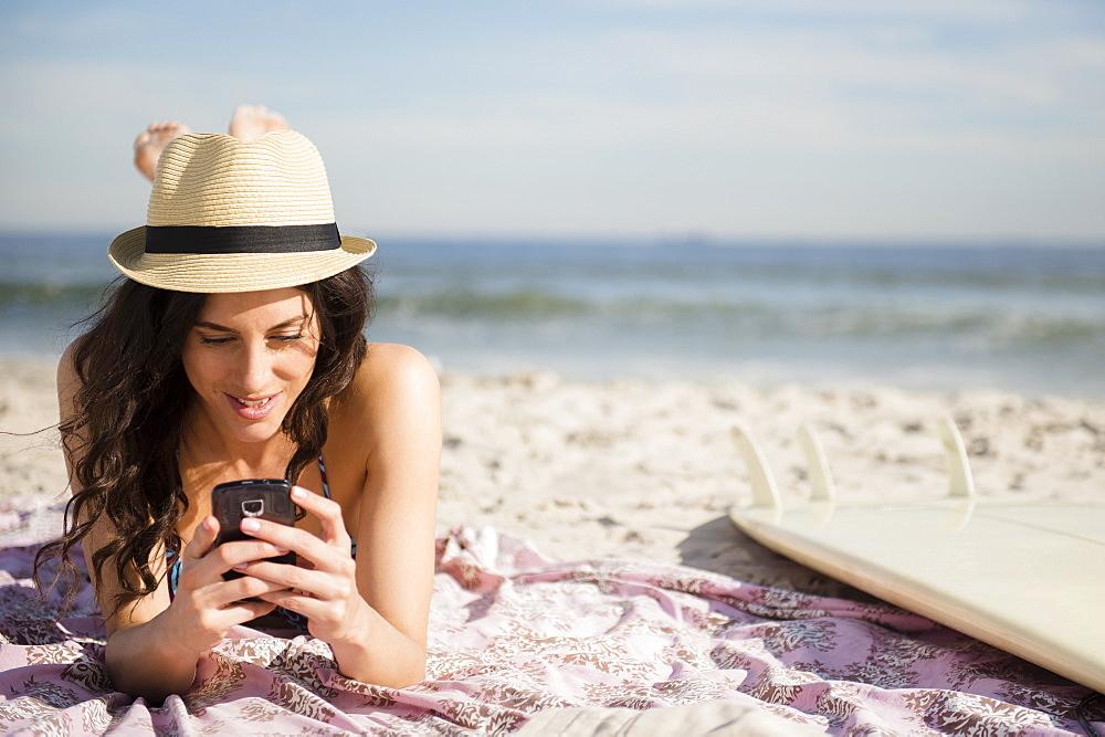 Woman using cell phone on beach, Rockaway Beach, New York