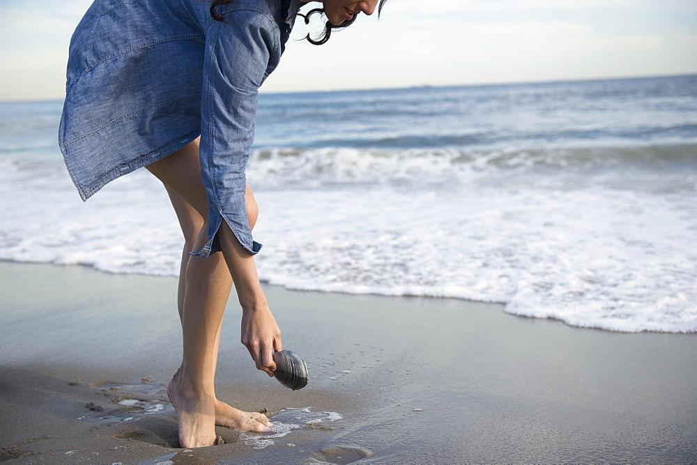 Woman collecting seashells on beach, Rockaway Beach, New York