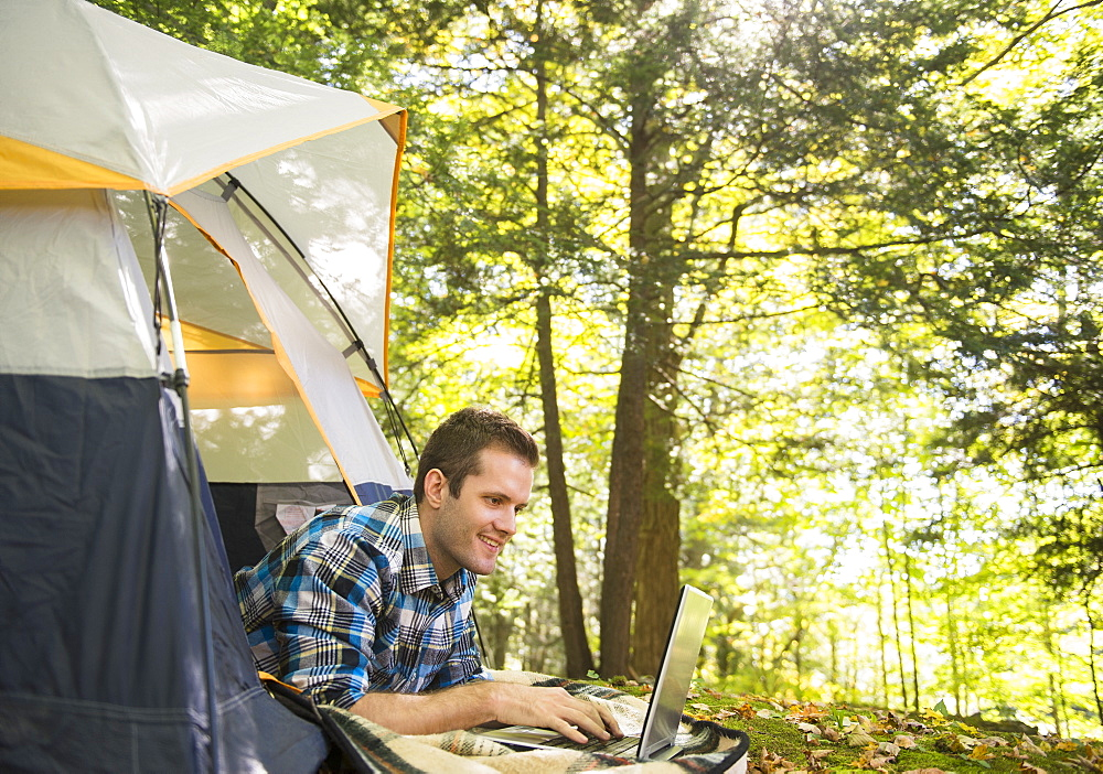Man using laptop outside tent, Newtown, Connecticut