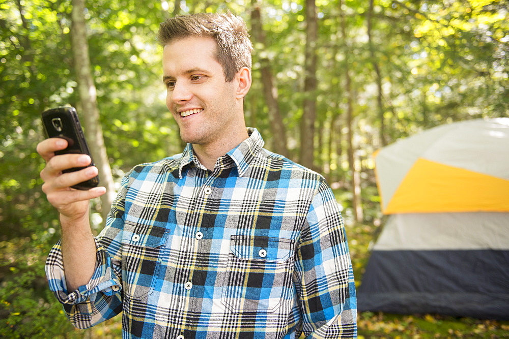 Man using cell phone in forest, Newtown, Connecticut