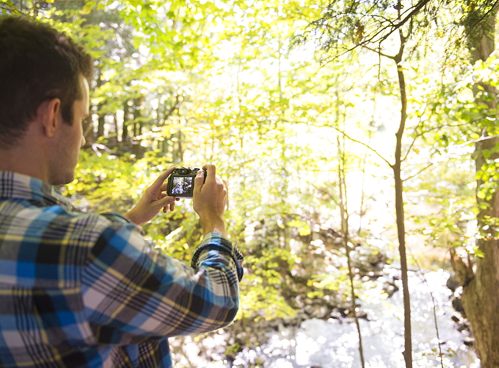 Man taking picture in forest, Newtown, Connecticut