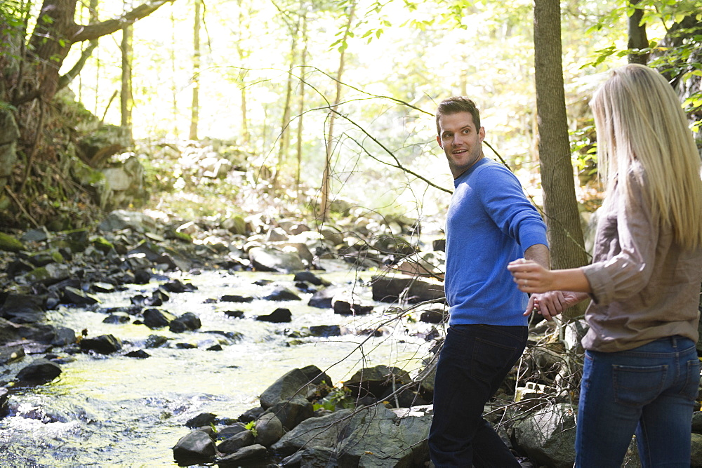 Couple walking by stream in forest, Newtown, Connecticut