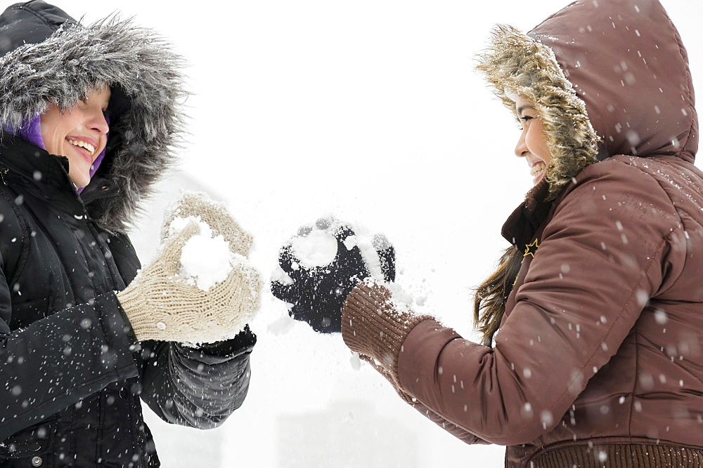 Two young women having snowball flight