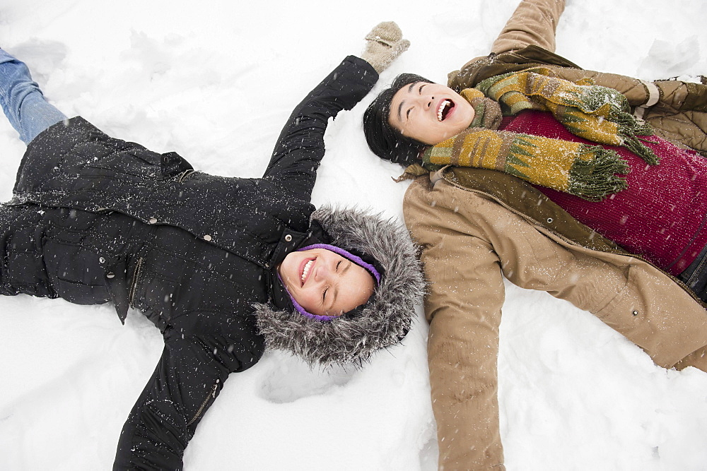 Two young people making snow angels