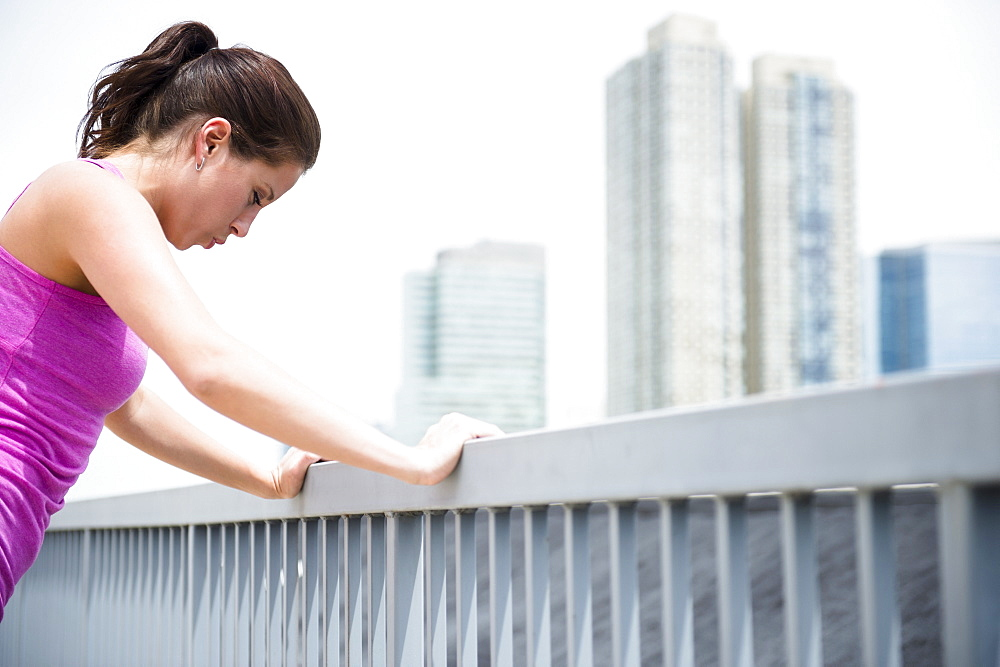Young woman stretching by railing
