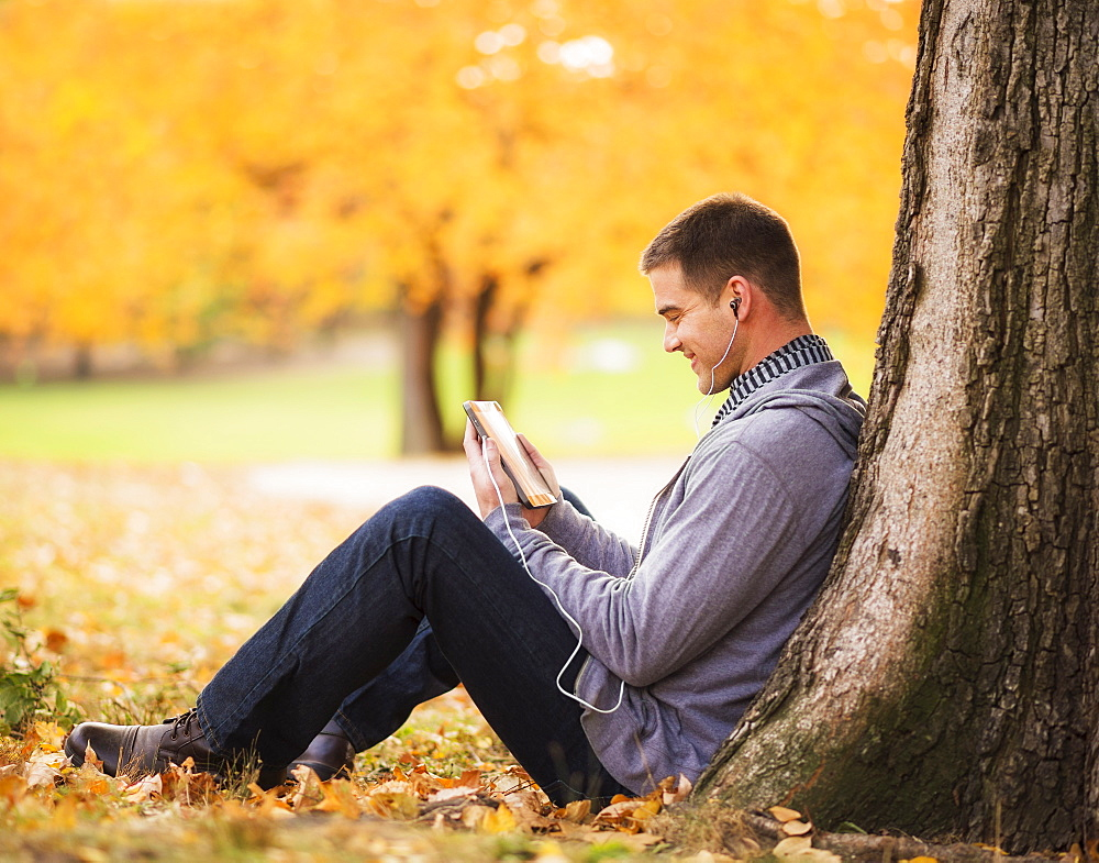Young man using digital tablet in Central Park, USA, New York State, New York City