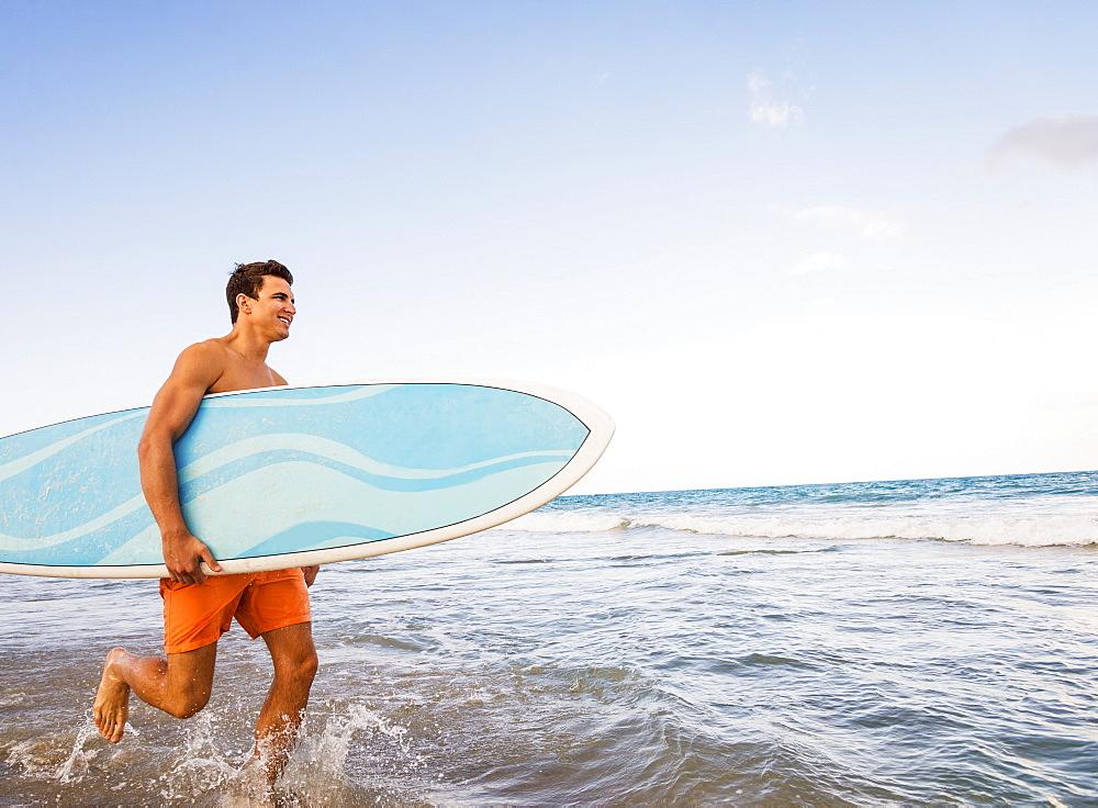 Young man carrying surfboard, Jupiter, Florida, USA