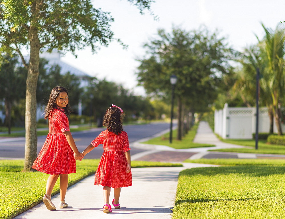 Back view of girls( 4-5, 8-9) holding hands, Jupiter, Florida