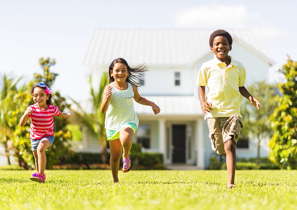 Girls( 4-5, 8-9) and boy (6-7) playing on front yard, Jupiter, Florida