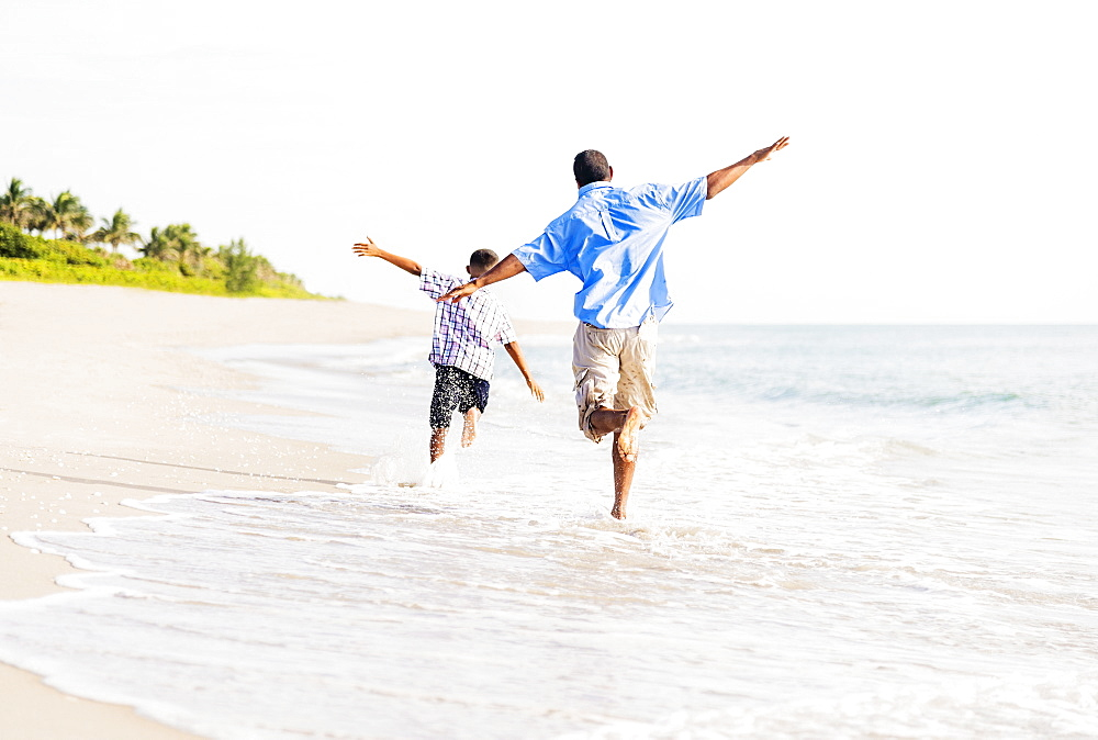 Father and son (10-11) running on beach, Jupiter, Florida