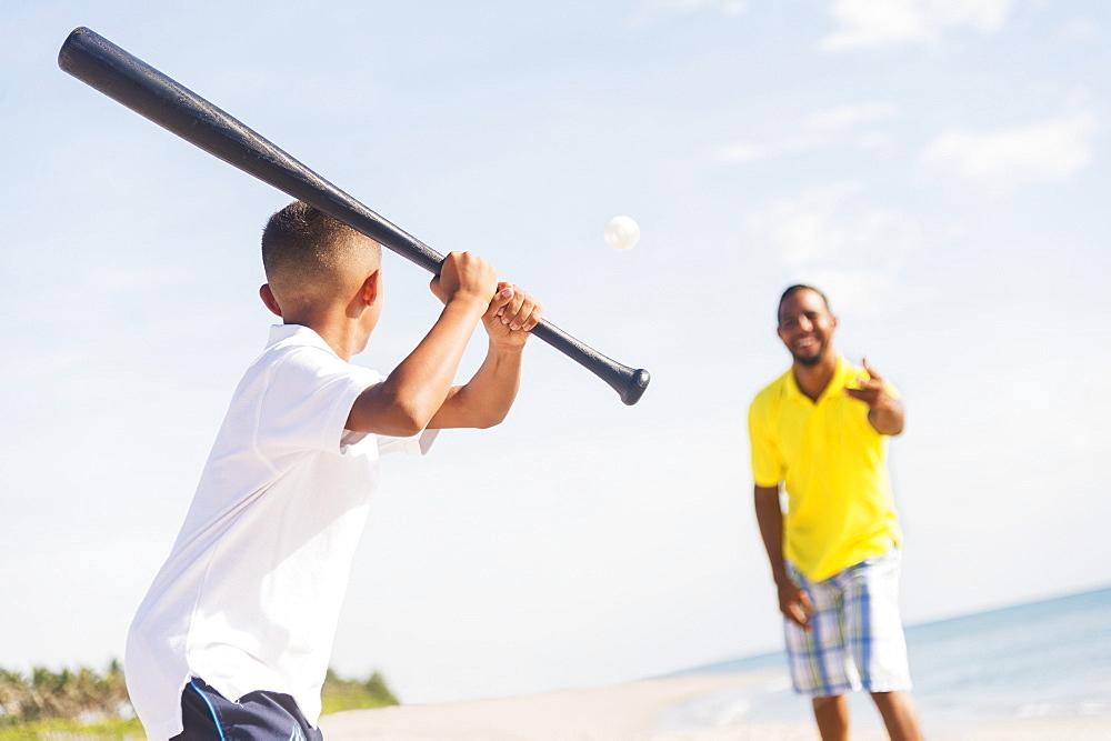 Father and son (10-11) playing baseball on beach, Jupiter, Florida