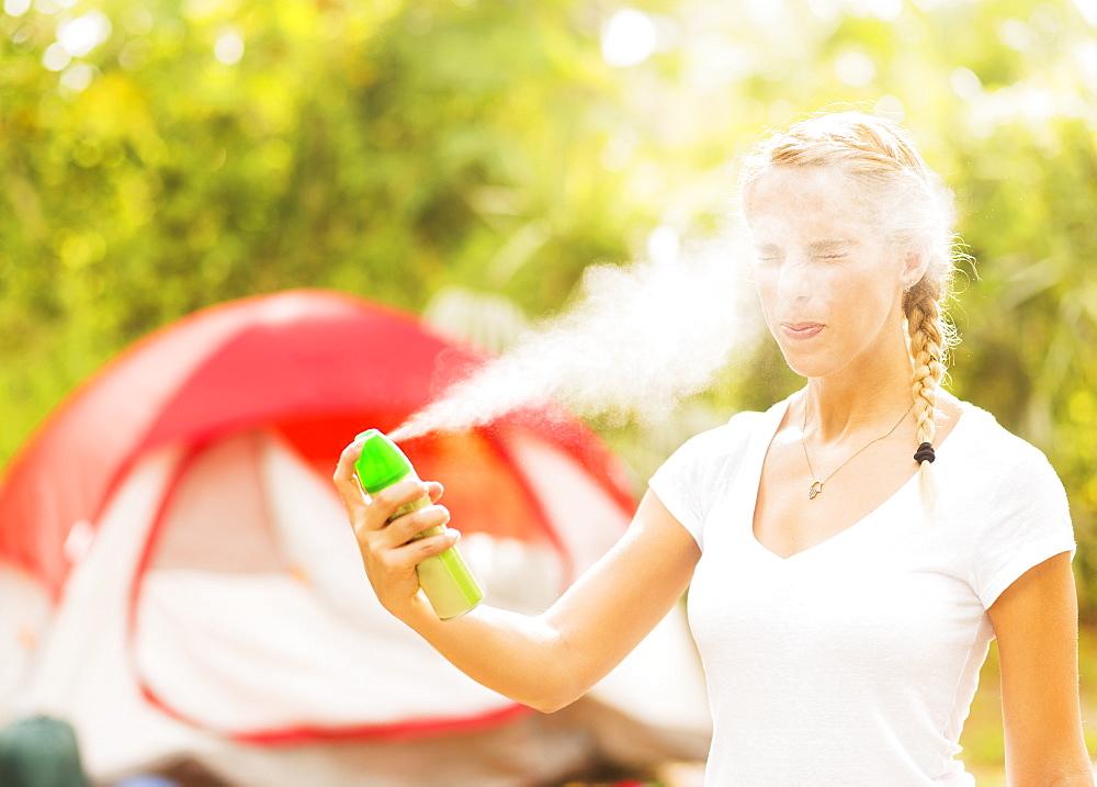 Woman spraying head with bug spray