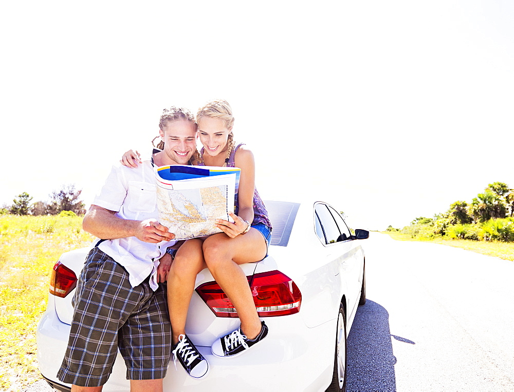 Couple at back of car looking at map, Tequesta, Florida
