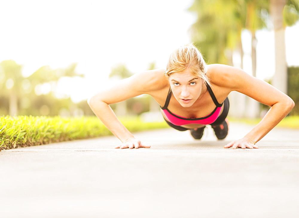 Woman doing pushups outdoors, Jupiter, Florida