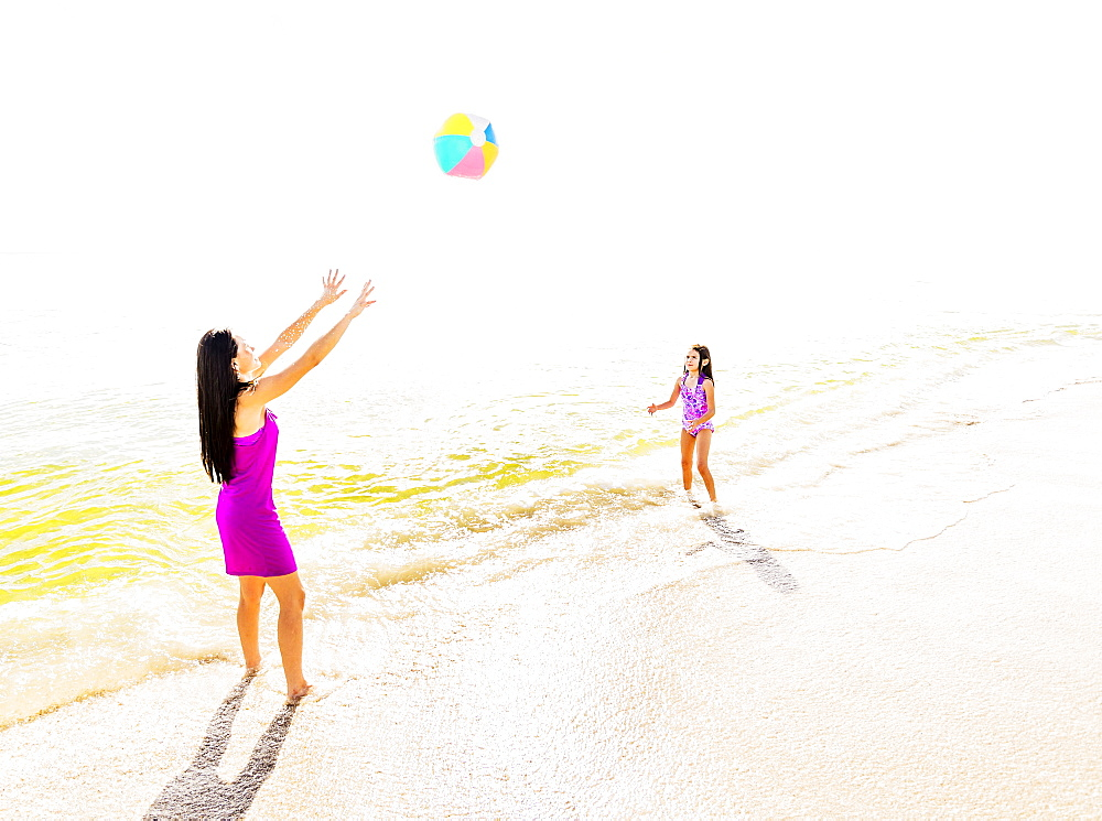 Mom throwing beach ball to her daughter (6-7) on beach, Jupiter, Florida