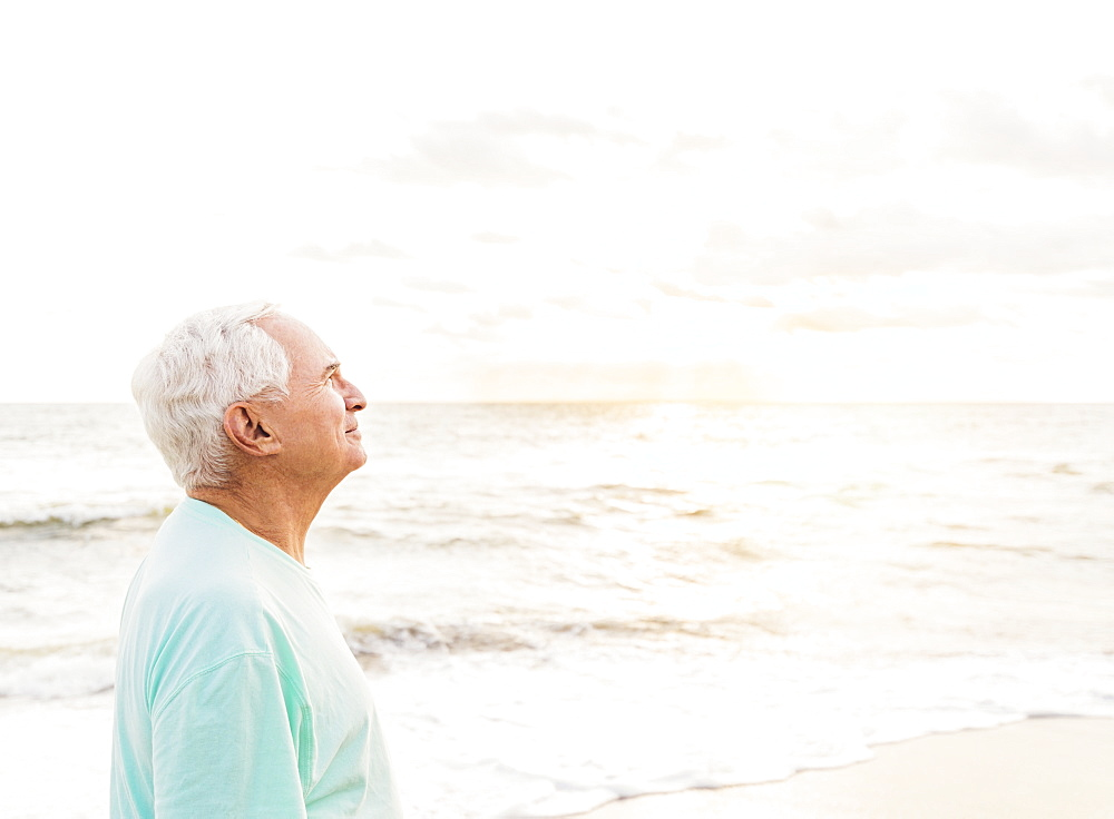 Side view of senior man smiling on beach, Jupiter, Florida
